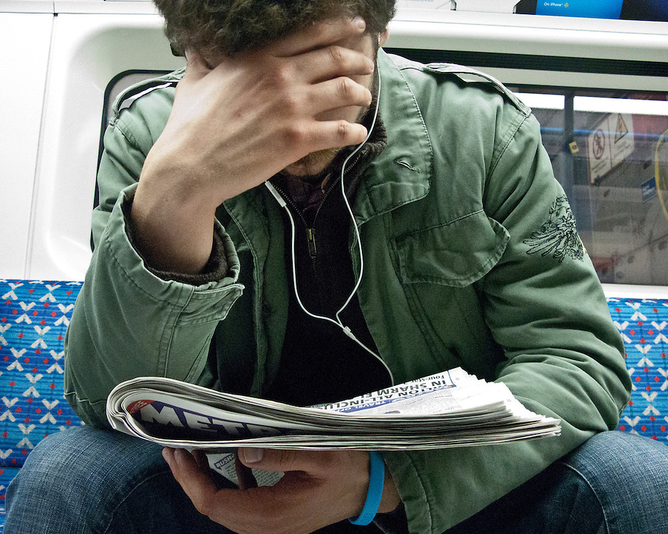 Portrait of a man listening to music and reading a newspaper with hand over his face