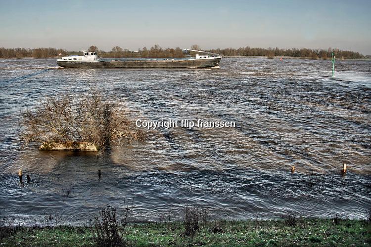 Nederland, Millingen, 10-2-2020 In de rivier de Waal is het verhoogd water. Het rivierwater is de uiterwaarden ingelopen en staat tot aan de voet van de dijk . Een binnenvaartschip vaart voorbij . Foto: Flip Franssen
