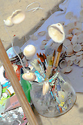 Arts and Crafts concept. Paint brushes, paints and shells on the beach