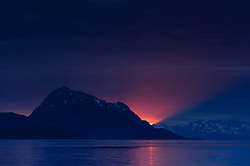 The last ray of sunlight from the setting sun basks on the Sitakaday Narrows in the main bay of Glacier Bay National Park and Preserve in this view seen from Young Island located in the Beardslee Islands of the park in southeast Alaska. At left is Marble Mountain, and in the far background is Mount Abdallah.