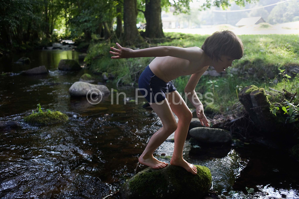 Wearing his bathing costume, a young adventurer clambers over rocks in the Gross Enz river in Germany's Black Forest. The lad of 10 crouches to better balance himself, carefully placing his bare feet on the slippery rock's surface as he emerges from the chilly mountain water. It is high summer and we can see the boy backlit by the glare of strong sunlight in the background. The Gross Enz river rises in Enzklosterle in Baden-Württemberg and is an eventual  tributary of the Neckar. Geologically, the Black Forest consists of a cover of sandstone on top of a core of gneiss. During the last glacial period, the Würm glaciation, the Black Forest was covered by glaciers.