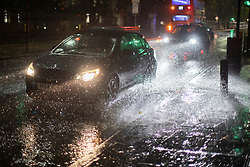 © Licensed to London News Pictures. 20/10/2021. London, UK. A car drives through a large puddle during heavy rain in Greenwich South East London. An Amber weather warning for rain is in place for parts of London and South East England.  Photo credit: George Cracknell Wright/LNP