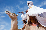 A nomad riding a dromedary against a cloudy blue sky in the Sahara desert of Morocco.