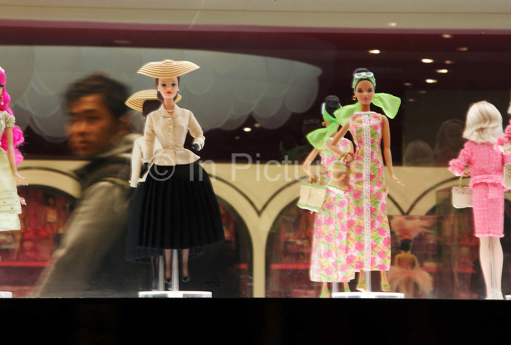 A visitor walks past Babie dolls on display during the Media Sneak Preview of the new Barbie Shanghai flagship store in Shanghai, China on 20 February 2009.  The Barbie store has become a hit in Shanghai as a place where doting mothers take their daughters, often the only child in the family, for a girls' day out.