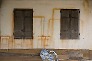 house's facade with shutters closed and brown paint marks remaining on the wall. Bac Ninh province, Vietnam, Asia.
