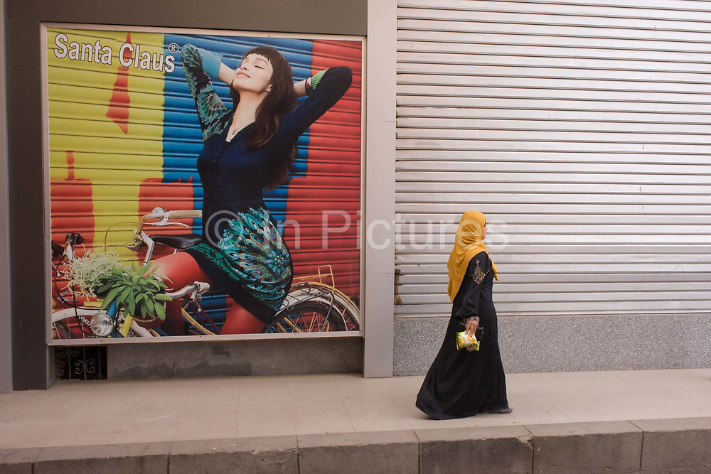 A traditionally-dressed Muslim woman walks past a poster for stylish arabic clothing in the city of Luxor, Nile Valley, Egypt. Wearing her veil and a long dress the lady observes the modesty demanded by her religion as opposed to the female on the poster, the Westernised style.