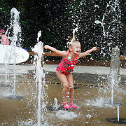 Elyse Lollings, 4, of Ohio, splashes through the fountain at Coligny Beach Park before heading to the beach with family on April 23, 2015.