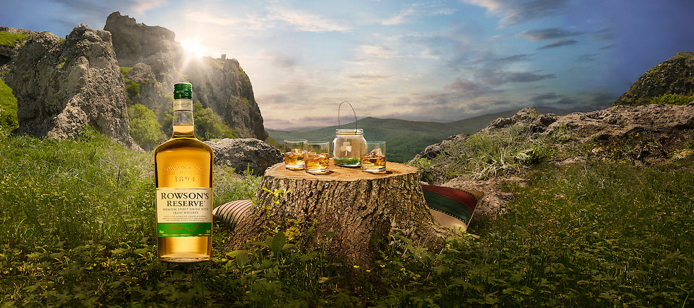 A bottle of Irish whiskey next to a tree stump used as a table with glasses on and cushions to sit on Ray Massey is an established, award winning, UK professional  photographer, shooting creative advertising and editorial images from his stunning studio in a converted church in Camden Town, London NW1. Ray Massey specialises in drinks and liquids, still life and hands, product, gymnastics, special effects (sfx) and location photography. He is particularly known for dynamic high speed action shots of pours, bubbles, splashes and explosions in beers, champagnes, sodas, cocktails and beverages of all descriptions, as well as perfumes, paint, ink, water – even ice! Ray Massey works throughout the world with advertising agencies, designers, design groups, PR companies and directly with clients. He regularly manages the entire creative process, including post-production composition, manipulation and retouching, working with his team of retouchers to produce final images ready for publication.