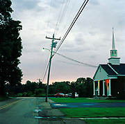 "Road side baptist Church in Arkabutla, Senatobia. You can't drive through the southern states, 'Bible belt"" of America without passing lots of churches. This really is a God fearing part of the world with religion everywhere: in the gospel music, sermons on the radio and lots of vast signs on the road advertising directly for your soul. Pictured here is a is typical wooden built chapel photographed as the light begins to fade."