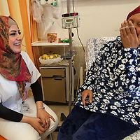 Rasmieh Awawdeh from Ramallah shares a joke with nurse Tasmin Tarayrah on the Hematology Ward of the Augusta Victoria Hospital in Jerusalem. On his hand is written the word 'Hope'. The Augusta Victoria Hospital is located on the southern side of Mount of Olives in East Jerusalem and is run by the Lutheran World Federation, LWF.