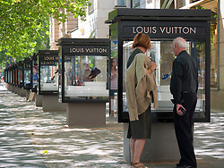 Couple looking at luxury products in glass display cabinet at Louis Vuitton boutique on Kurfurstendamm Charlottenburg Berlin Germany