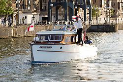 © Licensed to London News Pictures. 16/05/2015. London, UK. The skipper of Dunkirk Little Ship, Chumley waves as he parades in Royal Victoria Dock this evening. Over 20 Dunkirk Little Ships have gathered in London toay before leaving in the morning to continue their journey to Dunkirk to mark the 75th anniversary of the Dunkirk Evacuations. Photo credit : Vickie Flores/LNP