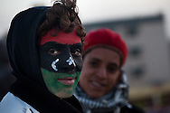 A boy painted his face with the old flag of Libya before Qadaffi in the main square of Tabrurk where people are demanding Qadaffi to leave on Feb. 24, 2011. The square has become a symbol of New Libya, tents have been set up, people are giving out free food, and heavy equiptment is being used to repair the square.