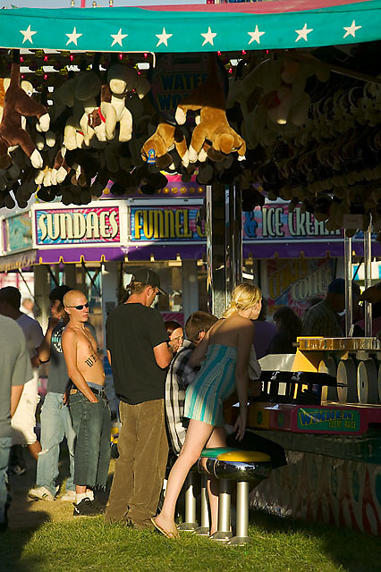 A bald,shirtless young man with a tattoo on his chest and wearing sunglasses glances at a young woman at the Western Idaho Fair