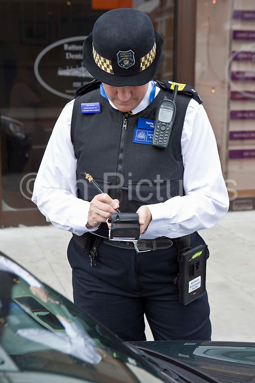 A Metropolitan Police traffic warden gives a ticket out on the Red Route in Battersea.