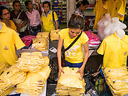 04 DECEMBER 2012 - BANGKOK, THAILAND: A vendor wearing yellow sells yellow tee shirts in front of Siriraj Hospital. Yellow is the official color of the Thai King, who celebrates his 85th birthday Wednesday, Dec. 5. The King lives in Siriraj. He is expected to make a rare public appearance and address the nation from Mukkhadej balcony of the Ananta Samakhom Throne Hall in the Royal Plaza. The last time he did so was in 2006. His birthday is a public holiday in Thailand and hundreds of thousands of people are expected to jam the streets around the Royal Plaza and Grand Palace to participate in the festivities.    PHOTO BY JACK KURTZ