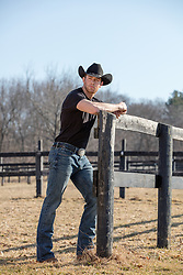 cowboy leaning on a rustic fence