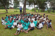 At Nyamiyaga primary school the Bwindi Community Hospital run health outreach programs. Reverend Sam, Head of Community Health, works on a sight test game with the children. As part of the outreach programme they cover 32 primary schools and 5 secondary schools in the region as well as many communities. The main Bwindi Community Hospital is in Buhoma village on the edge of the Bwindi Impenetrable Forest in Western Uganda. It serves around 60,000 people from the surrounding area.