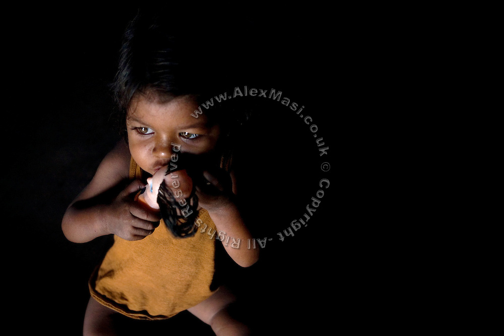 Meenakshi, 7, a child born with mental and physical disabilities from a gas-affected mother is kissing her only doll while inside her home in the impoverished Oriya Basti Colony, in Bhopal, Madhya Pradesh, near the abandoned Union Carbide industrial complex.