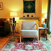 A blue grey danish modern chair on an Oriental carpet, in a yellow room, with a mandala behind it on the wall and a dark brown sofa on the left.
