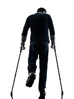 one man injured man walking with crutches rear view in silhouette studio on white background