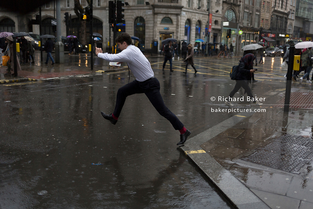 Storm Georgina swept across parts of Britain and in central London, lunchtime office workers were caught out by torrential rain and high winds, on 24th January 2018, in London, England. Pedestrians resorted to leaping across deep puddles at the junction of New Oxford Street and Kingsway at Holborn, the result of overflowing drains. Fourth in a sequence of five photos.