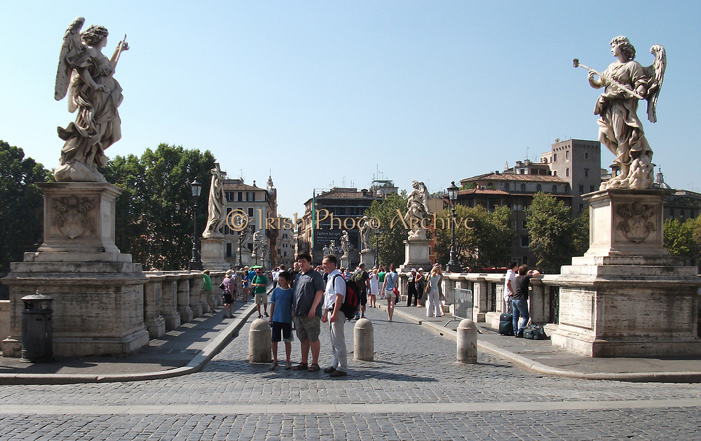 Tourists stood on the Ponte Sant'Angelo, (Formerly called the Aelian Bridge) a bridge spanning the Tiber in Rome, Italy. It was completed in 134 AD by Roman Emperor Hadrian, and it links the city centre to his former mausoleum, which is now the Castel Sant'Angelo. the bridge is adorned with colossal statues of angels holding the instruments of passion.
