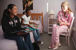 Teenage girls in bedroom with magazines.