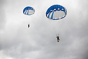 """Forest Service smokejumpers throughout the United States have jumped with circular parachute canopies since 1939, although square canopies were developed in the 1960s and '70s and are currently used by smokejumpers who work for the Bureau of Land Management. Square-shaped canopies behave more like a wing, requiring forward speed in order to stay aloft. Circular canopies rely primarily on drag, making it easier for a jumper to drop straight down. There are pros and cons to both designs: While circular canopies can descend at a nearly vertical trajectory, they become difficult to control when the wind blows faster than 10 mph. The BLM's square models, sometimes called """"ram-air"""" chutes because they behave like airfoils, remain maneuverable at twice that speed."""