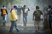 26 DECEMBER 2013 - BANGKOK, THAILAND: People walk through clouds of tear gas near the Thai Japan Stadium in Bangkok. Thousands of anti-government protestors flooded into the area around the Thai Japan Stadium to try to prevent the drawing of ballot list numbers by the Election Commission, which determines the order in which candidates appear on the ballot of the Feb. 2 election. They were unable to break into the stadium and ballot list draw went as scheduled. The protestors then started throwing rocks and small explosives at police who responded with tear gas and rubber bullets. At least 20 people were hospitalized in the melee and one policeman was reportedly shot by anti-government protestors.      PHOTO BY JACK KURTZ