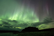 The Aurora seems to circle above an island in Bartlett Cove, Alaska