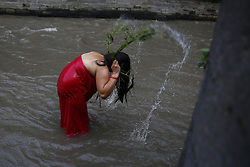 September 6, 2016 - Kathmandu, Nepal - A Nepalese Hindu woman takes a ritual bath lashing with leaves of the Aghada plant that is considered sacred during Rishi Panchami festival on the banks of Bagmati River inside Pashupathinath Temple premise, a UNESCO World Heritage Site in Kathmandu, Nepal on Tuesday, September 6, 16. Rishi Panchami is observed to mark the end of three-day Teej festival when women worship Sapta Rishi (Seven Saints) on the last day to wash off one's impurity for the whole year. (Credit Image: © Skanda Gautam via ZUMA Wire)