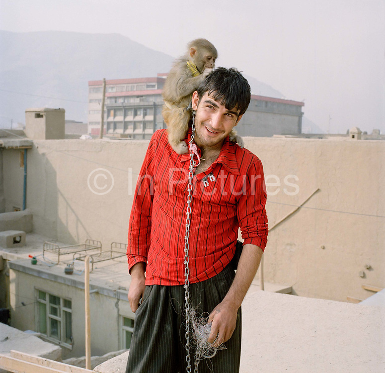 """Mustafa, aged 19 (although he is unsure of exact age) is a labourer on the Turquoise Mountain project rebuilding the old town centre, Murad khane. He is single and lives with his parents. The monkey is called Shadi. <br /> <br />  """"Before Turquoise Mountain came here it was very bad. Everywhere smelt, it was full of rubbish and the sewage – people just threw it out in front of their houses - Before I was just polishing shoes, now I get $5 dollars a day.""""<br /> <br />  The charity was set up by Rory Stewart. He was asked personally by Prince Charles to take on the task of rebuilding the ancient heart of Kabul. His charity using local labour and the goodwill of the community is substantially into the task and has also set up a school training Afghans in traditional crafts. The area had literally been turned into a rubbish dump, now though using ancient skills the buildings are being restored to their former glory, Stewart is hopeful that he can contribute significantly to the local economy."""