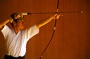 A kyudo practitioner draws his bow towards the target at the Kyoto Budo Centre dojo.Kyudo is a modern Japanese martial art derived from ancient Samurai archery, heavily influenced by Zen Buddhist philosophy.