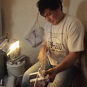 Tommy Coates works on walrus ivory, carving a Snowy Owl figurine. Barrow, Alaska