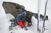 A skier cooks dinner in a snow storm at a camp near Sky Top Lakes, on the approach to Granite Peak, Beartooth Mountains, Montana.