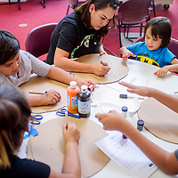 Crystal Gordo, center, helps Cade Brown and her other children make their shields during a workshop at the Navajo Nation Museum in Window Rock Thursday.