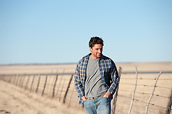 handsome man alone on a ranch with a rustic fence