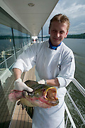 Chef Rafael bauch proudly presenting a huge, freshly caught catfish sold to him by local fishermen, while the ship goes along the Rumanian side (l.)..M.S. Johann Strauss, a brand new four star+ river cruiser operated by Austrian River Cruises, and chartered by Club 50 (a travel agency especially for seniors aged 50 and up) undertook an epic 3-week journey (May 21 to June 10, 2004) all the way from Amsterdam to the Black Sea?along Rhine, Main and Danube?, presumably the first passenger vessel ever to have done so. This is one of the images recorded during this historic voyage.