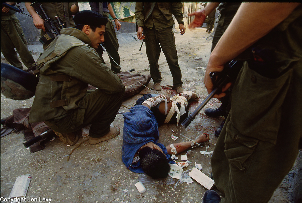 A Palestinian boy laies bleeding from gunshot wounds as Israeli soldiers look on.