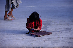 A young girl counting her money on the road