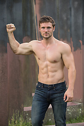 shirtless muscular man leaning against steel