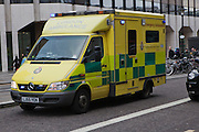 Paramedics driving a London ambulance  along the street at speed in response to an emergency call out.