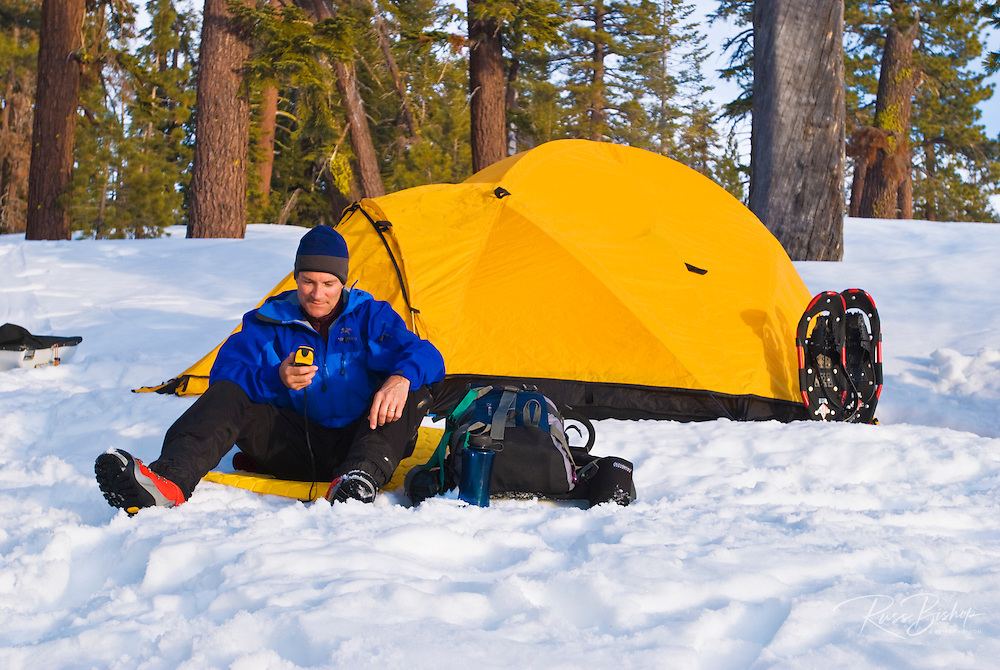 Backcountry skier (using a GPS) and yellow dome tent, Yosemite National Park, California
