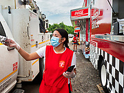 """26 JUNE 2020 - DES MOINES, IOWA: NADINE GARCIA, a worker at Fair Food Friday in Des Moines, hands a turkey leg to a customer. The 2020 Iowa State Fair, like many state fairs in the Midwest, has been cancelled this year because of the COVID-19 (Coronavirus) pandemic. The cancellation of the fair left many small vendors stranded with no income. Some of the fair food vendors in Iowa started """"Fair Food Fridays"""" on a property a few miles south of the State Fairgrounds. People drive up and don't leave their cars while vendors bring them the usual midway fare; corndogs, fried tenderloin sandwiches, turkey legs, deep fried Oreos, lemonaide and smoothies. Fair Food Friday has been very successful. The vendors serve 450-500 people per Friday and during the lunch rush people wait in line in their cars 30 - 45 minutes to place an order.      PHOTO BY JACK KURTZ"""