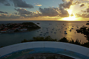 High view of the sunset over the boats in Gustavia port with porcelain semi-circular map guide in foreground, St. Barthelemy, FWI