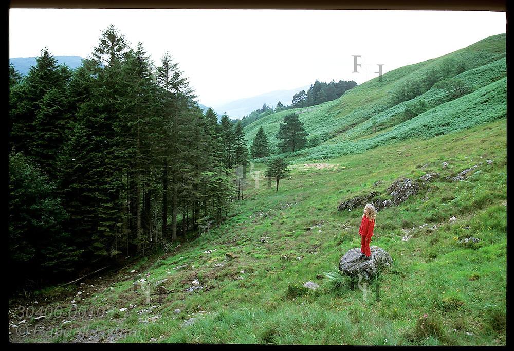 Little girl stands on rock above Clachaig Gulley, Harry Potter's Prisoner of Azkaban movie film site for Hagrid's Hut; Glencoe, Scotland.