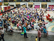 25 JUNE 2016 - BANGKOK, THAILAND: People watch traditional entertainment in the main concourse area of Hua Lamphong train station during the station's centenary celebration. Hua Lamhong opened on June 25, 1916 after six years' construction. The station was built in an Italian Neo-Renaissance-style, with decorated wooden roofs and stained glass windows. The architecture is attributed to Turin-born Mario Tamagno. There are 14 platforms, 26 ticket booths, and two electric display boards. Hua Lamphong serves over 130 trains and approximately 60,000 passengers each day. Since 2004 the station has been connected by an underground passage to the MRT (Metropolitan Rapid Transit) subway system's Hua Lamphong Station.     PHOTO BY JACK KURTZ