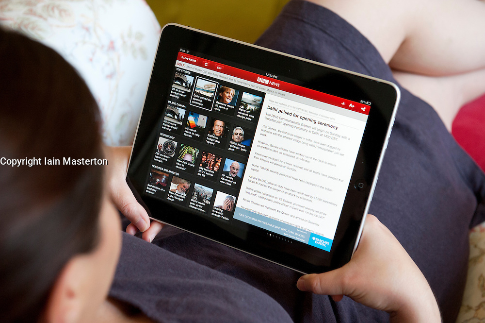 Woman reading news on BBC online news application on an iPad tablet computer