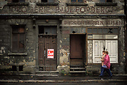 Six months after the fall of the Berlin Wall and the end of the Communist Eastern Bloc, two east German women walk past a closed and decaying Pharmacy and photography business where a poster advertising a New Germany weekly newspaper has been attached to a rotting door, on 15th June 1990, in Zwickau, eastern Germany former DDR.